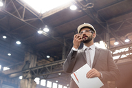 Manager with walkie-talkie in steel factory - CAIF09841
