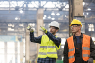 Steel workers talking and pointing in factory - CAIF09859