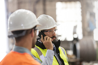 Steel workers talking on cell phone in factory - CAIF09862