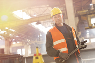Portrait confident steel worker holding large wrench in factory - CAIF09874