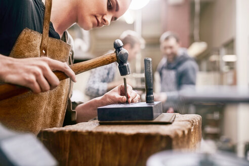 Jeweler using hammer in workshop - CAIF09877