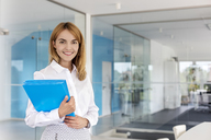 Portrait smiling businesswoman holding folders in conference room - CAIF09916