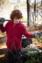 Boy holding garden fork in forest - CAVF04863