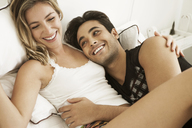 Cheerful couple lying on bed at home - CAVF04887