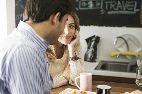 Woman looking at man while leaning on table at kitchen - CAVF04899