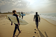 Friends carrying surfboards while walking on sand at beach - CAVF04926