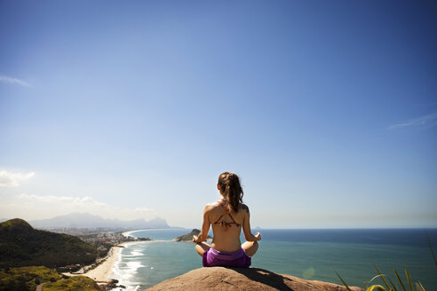 Woman meditating while sitting on rock by sea - CAVF04989
