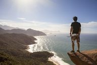 Rear view of hiker standing cliff by sea - CAVF04992
