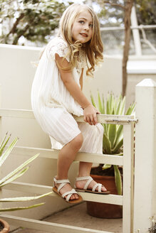 Girl looking away while sitting on railing - CAVF05004