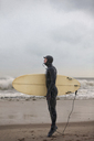 Side view of man holding surfboard while standing at shore - CAVF05085
