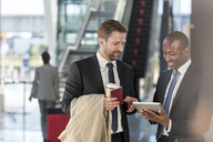 Businessmen with digital tablet talking in airport - CAIF10023
