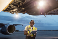Airport ground crew worker with clipboard under airplane on tarmac - CAIF10026