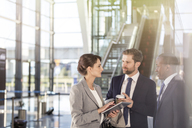 Business people with digital tablet talking in airport - CAIF10038