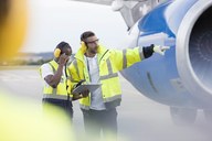 Air traffic controllers with clipboard next to airplane on airport tarmac - CAIF10041