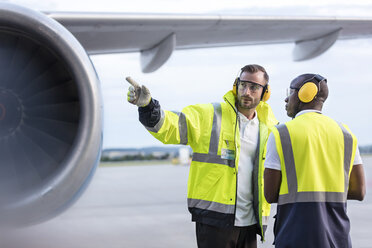 Air traffic control ground crew workers talking near airplane on airport tarmac - CAIF10047