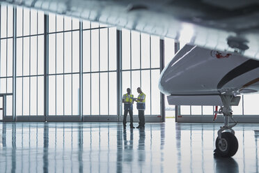 Air traffic control ground crew workers talking in airplane hangar - CAIF10050
