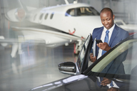 Businessman with cell phone getting into car near corporate jet in hangar - CAIF10053