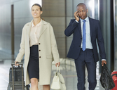 Business people walking with luggage in airport concourse - CAIF10059