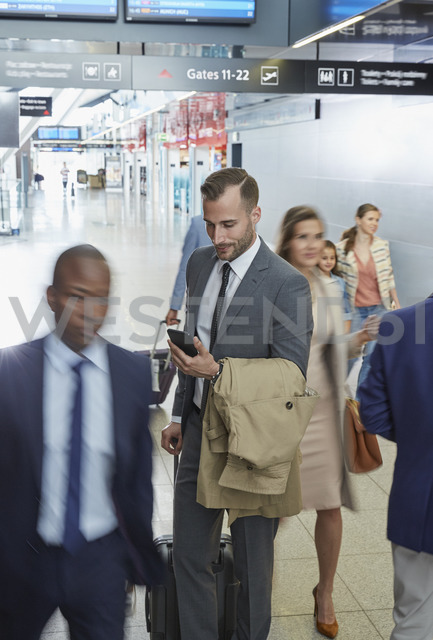 Businessman using cell phone in airport concourse - CAIF10062