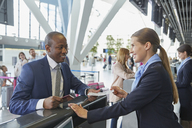 Customer service representative helping businessman at airport check-in counter - CAIF10065