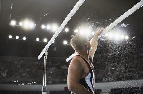 Male gymnast applying chalk powder to parallel bars - CAIF10101