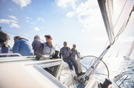 Retired friends on sailboat on sunny ocean - CAIF10149