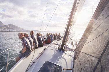 Retired friends sitting on sailboat on sunny ocean - CAIF10152