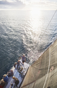 Friends sailing on sailboat on sunny ocean - CAIF10176