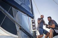 Men sailing pulling rigging equipment on sailboat - CAIF10182