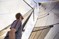 Man sailing looking up at sail - CAIF10185
