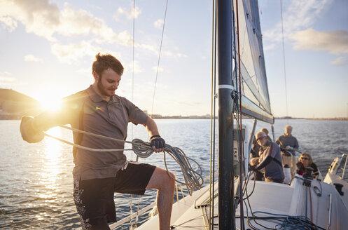 Man sailing looping rigging on sailboat - CAIF10188