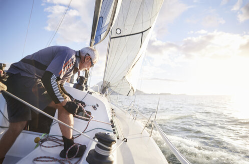 Man sailing pulling rigging on sailboat on sunny ocean - CAIF10191