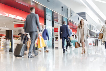 Travelers walking in airport concourse - CAIF10194