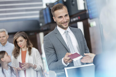 Businessman with passport at airport check-in counter - CAIF10200