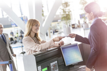 Customer service representative checking businesswoman ticket at airport check-in counter - CAIF10209