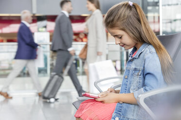 Girl using digital tablet in airport departure area - CAIF10212
