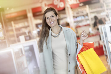 Smiling businesswoman leaving airport duty free shop with shopping bags - CAIF10215
