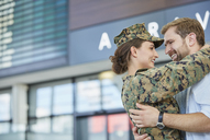 Husband greeting and hugging soldier wife at airport - CAIF10218