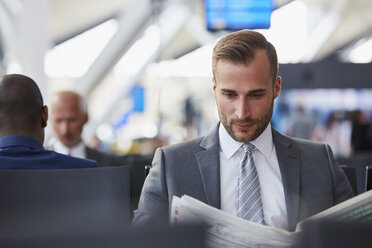 Businessman reading newspaper in airport departure area - CAIF10227