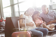 Pregnant family using digital tablet waiting in airport departure area - CAIF10230
