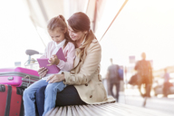 Mother and daughter using digital tablet on bench outside airport - CAIF10233