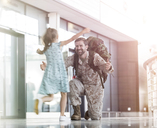 Daughter running and greeting soldier father in airport concourse - CAIF10239