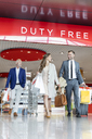 Business people leaving airport duty free shop with shopping bags and suitcase - CAIF10242