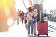 Father and daughter hugging outside airport - CAIF10245