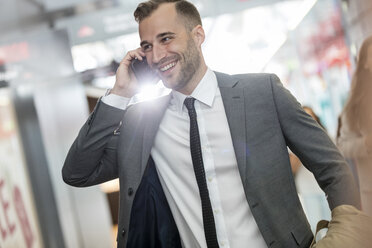 Smiling businessman talking on cell phone in airport - CAIF10257