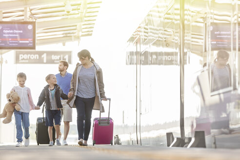 Family walking pulling suitcases in airport concourse - CAIF10266