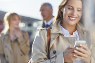 Smiling businesswoman texting with cell phone - CAIF10269