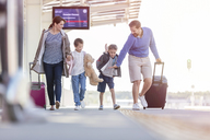 Family walking pulling suitcases at train station - CAIF10272