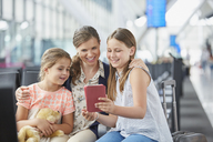 Mother and daughters using digital tablet in airport departure area - CAIF10281