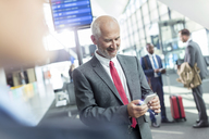 Businessman texting with cell phone in airport concourse - CAIF10287